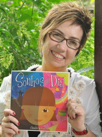 Foto vertical de uma mulher de meia idade segurando o livro Sonhos do Dia. Atrás dela, plantas