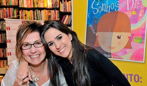Mãe e filha se abraçam e sorriem em uma livraria. Ao fundo, uma estante de livros e um cartaz. À direita, a capa do livro Sonhos do Dia, em formato ampliado.