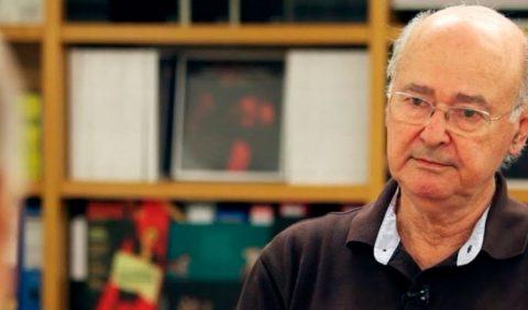 Homem de mai idade, calvo, de óculos, sentado em uma mesa, conversando com alguém. Ao fundo, uma estante de livros.