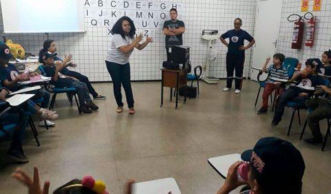 Mulher ao centro ensina Libras a várias crianças em uma sala de aula. Na parede, ao fundo, um quadro branco e uma tela com as letras do alfabeto. Dois adultos observam a cena do lado direito.