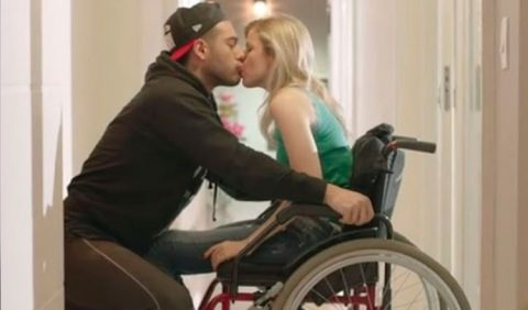 Foto de perfil de um casal se beijando na boca. Ela, à direita, em uma cadeira de rodas e ele, sentado para ficar na altura dela.
