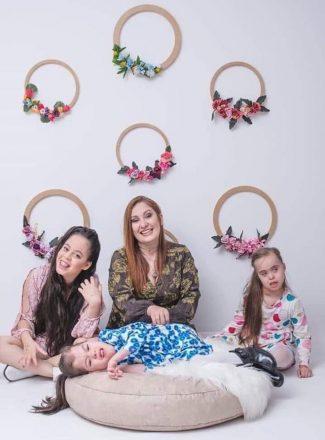 Foto vertical de uma mulher ao centro, duas garotinhas - uma de cada lada - e um terceira deitada em uma almofada redonda à frente. Ao fundo, seis círculos na parede com flores em cada um deles.