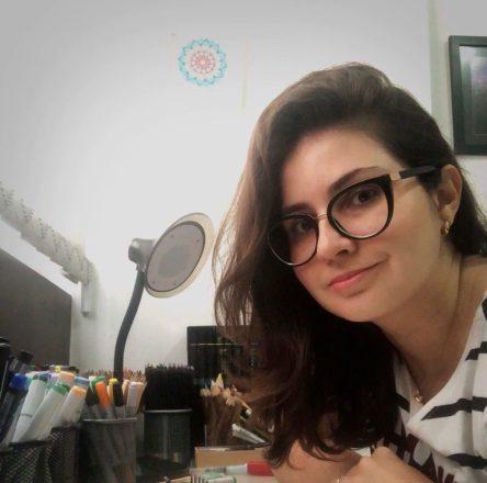 Foto quadrada de uma jovem sorrindo, de óculos, em um escritório, cercada de lápis coloridos organizados em pequenos potinhos.
