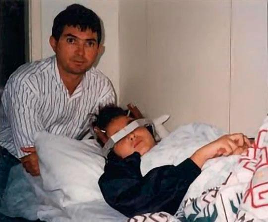 Jovem deitada em uma cama de hospital, enrolada em cobertores, com uma espécie de coroa na cabeça. Atrás dela, levemente curvado sobre a cama, seu pai.