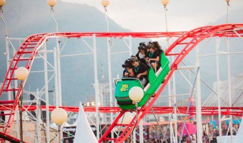 Foto de uma montanha russa pintada de vermelho e um carrinho verde com quatro pessoas usando óculos de realidade virtual, descendo a toda velocidade.