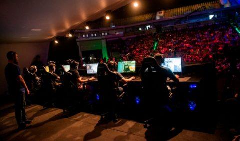 Foto bastante escura de cinco pessoas jogando vídeo game em computadores, um homem de pé atrás deles, observando, e uma grande platéia ao fundo.