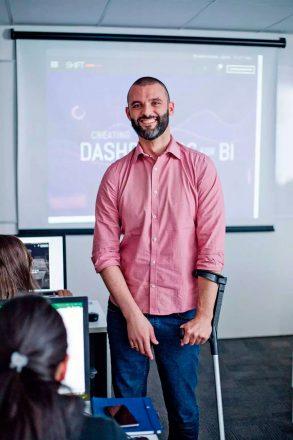 Foto vertical de um homem barbado, de pé, sorrindo, segurando uma muleta no braço esquerdo, em uma sala de aula.