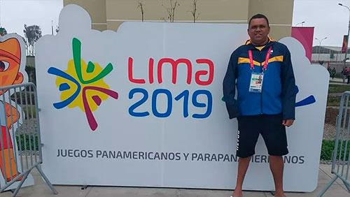 Homem de pé, do lado direito da fotografia, na frente de um cartaz branco, horizontal, escrito LIMA 2019 JUEGOS PANAMERICANOS Y PARAPANAMERICANOS