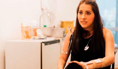 Mulher de 36 anos, sentada em uma cadeira de rodas, com um estetoscópio no pescoço e uma proteção ortopédica no braço esquerdo, fala com alguém em um consultório médico.