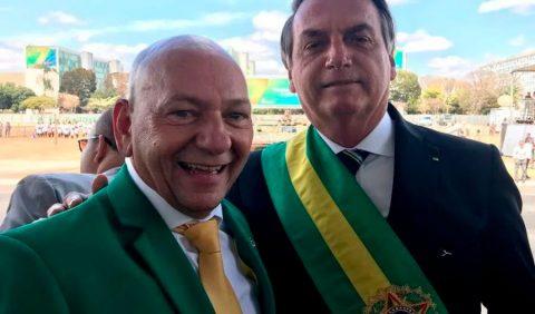 Dois homens, lado a lado, o empresário Luciana Hang, à esquerda, de paletó verde, blusa branca e gravata amarela e Jair Bolsonaro à direita, de paletó escuro e a faixa presidencial no peito.