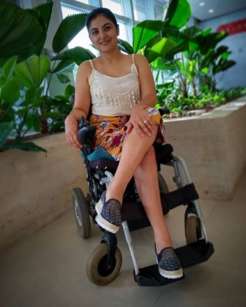 Foto vertical de uma mulher jovem sentada em uma cadeira de rodas, pernas cruzadas, sorrindo. Ao fundo, várias plantas.