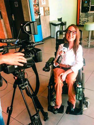 Foto vertical de uma mulher jovem sentada em uma cadeira de rodas, segurando um microfone e com uma câmera de filmagem a sua frente. Ela sorri, usa óculos e veste uma calça comprida goiaba e uma blusa branca de mangas compridas.