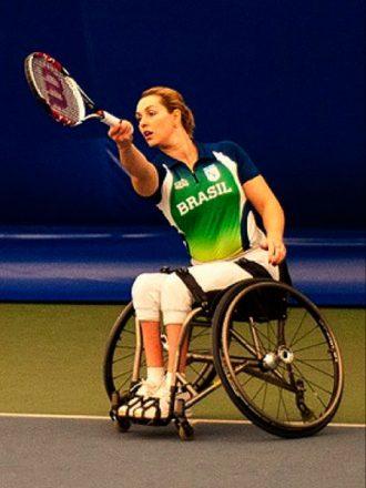 Mulher jovem, com o uniforme da seleção brasileira, joga tênis em uma cadeira de rodas.