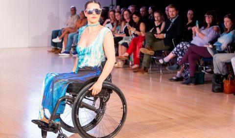 Desfile de moda com uma mulher em uma cadeira de rodas, no canto inferior esquerdo, usando um vestido com predominância de azul e óculos escuros. Do lado direito, várias pessoas assistem e fotografam.