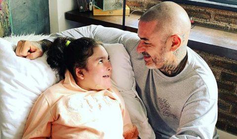 Pai e filha trocam um olhar carinhoso e amoroso um para o outro. A garotinha está deitada e ele, à direita, está curvado sobre ela.