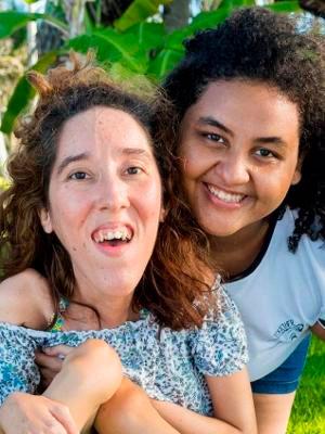 Duas garotas, lado a lado, olhando para a frente. À esquerda, a jovem possui uma doença congênita; à direita, sua namorada a abraça e sorri.