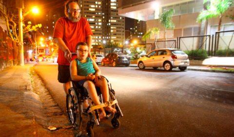 Pai e filho passeiam por uma rua de Belo Horizonte. O pai empurra a cadeira de rodas do garoto. Do lado direito da imagem, carros estacionados e luzes da rua, ao fundo.